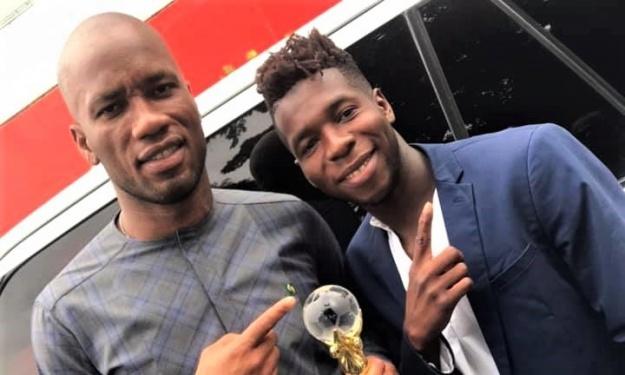 Titi Koné présente son trophée de Champion d'Afrique à Drogba